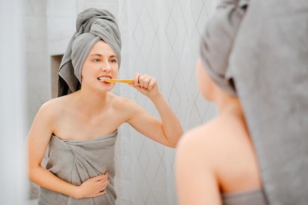 Frau mit einem handtuch auf dem kopf im badezimmer putzt sich die zähne zum aufhellen