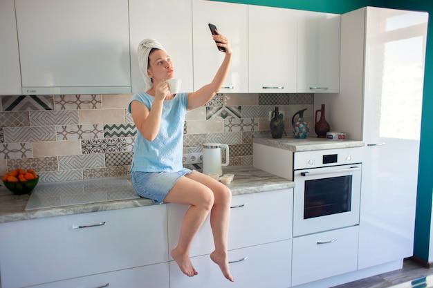 Frau mit einem handtuch auf dem kopf in ihrer küche beim frühstück und beim telefonieren