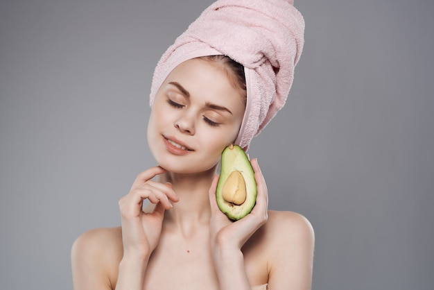 Frau mit einem handtuch auf dem kopf nach der dusche avocado posiert in nahaufnahme