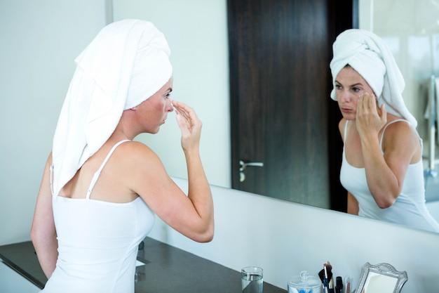 Frau mit einem handtuch auf dem kopf trägt gesichtscreme auf