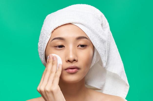 Frau mit einem handtuch auf dem kopf wischt ihr gesicht mit einem wattepad grün