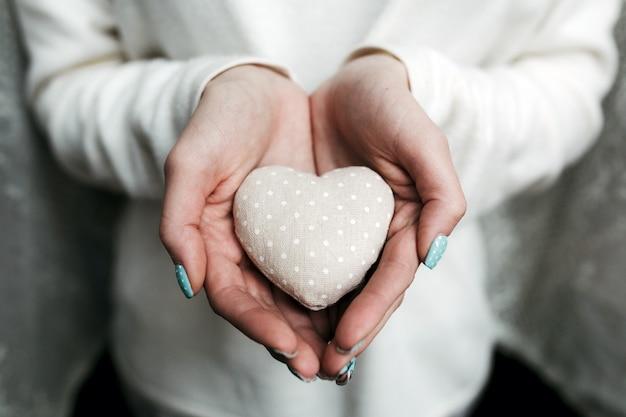 Frau mit einem herzförmigen stein in den händen