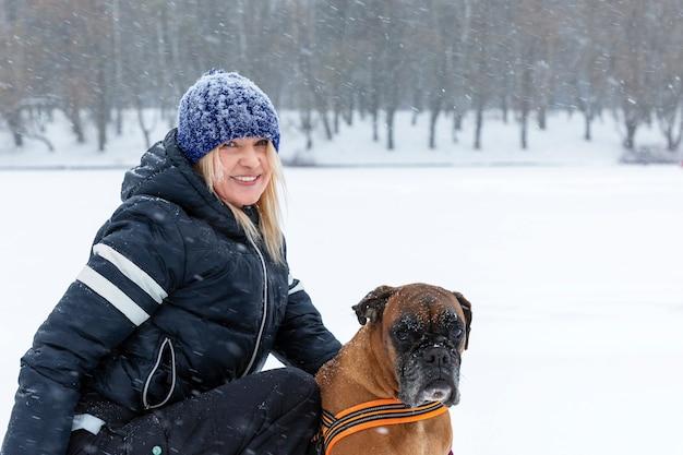 Frau mit einem hund an einem tag des verschneiten winters auf einem weg