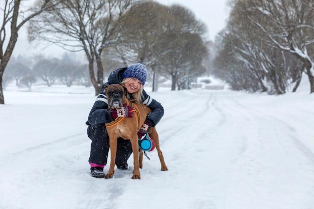 Frau mit einem hund auf einem spaziergang bei schneewetter