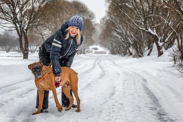 Frau mit einem hund, der im winterpark spielt. liebe und zärtlichkeit.