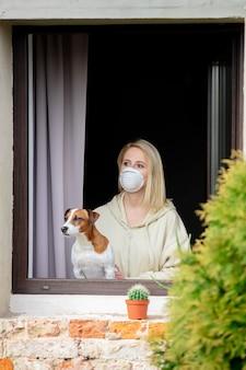 Frau mit einem hund sitzt am fenster während der quarantäne