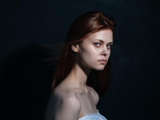 Frau mit einem interessierten blick auf ein dunkles hintergrundseitenansichtsmodell
