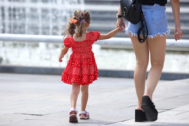 Frau mit einem kleinen mädchen in einem roten kleid, das die straße entlang geht