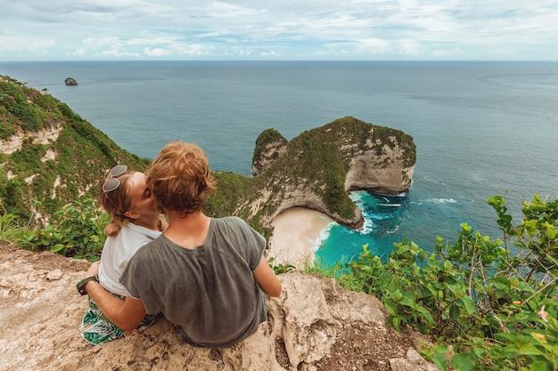 Frau mit einem mann am kelingking beach auf nusa penida bali indonesien