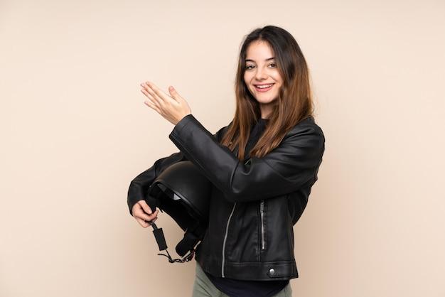 Frau mit einem motorradhelm auf beiger wand, die hände zur seite für einladung zum kommen ausdehnt