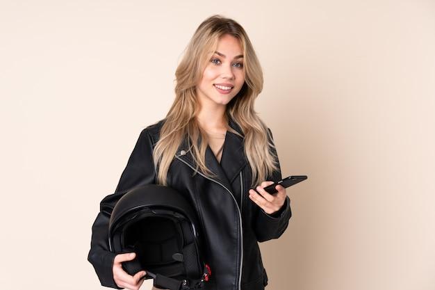 Frau mit einem motorradhelm lokalisiert auf beige wand, die kaffee zum mitnehmen und ein handy hält