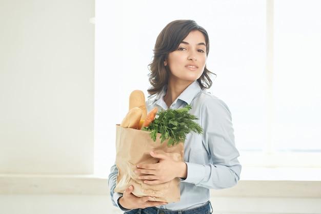Frau mit einem paket lebensmittel in der küche hausfrau gemüse gesundes essen