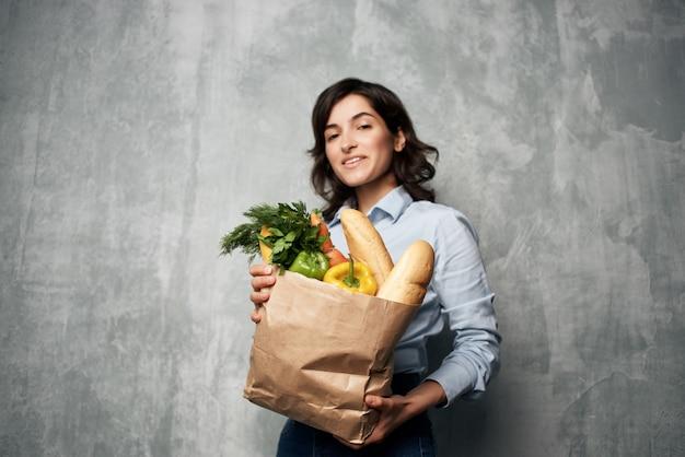 Frau mit einem paket lebensmitteleinkaufsgemüse. foto in hoher qualität