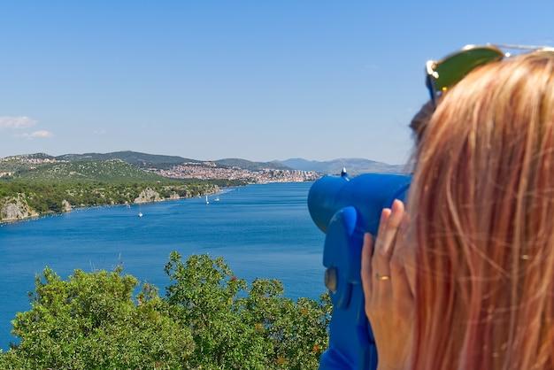 Frau mit einem panoramateleskop mit blick auf das mittelmeer