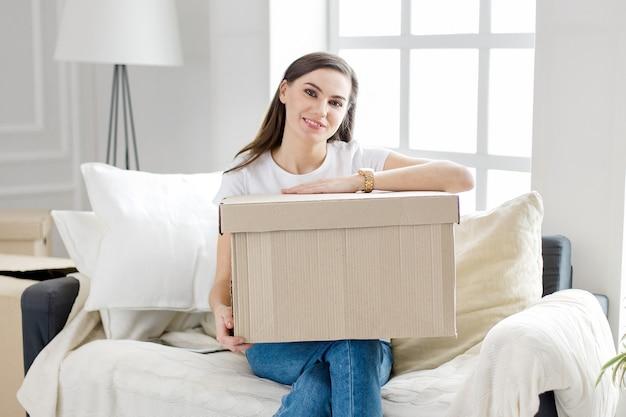 Frau mit einem pappkarton sitzt auf dem sofa