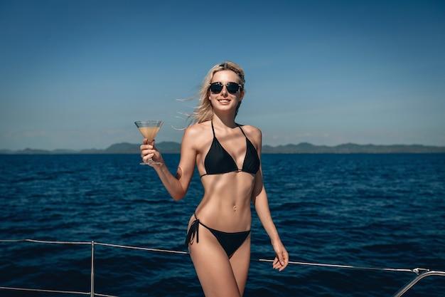 Frau mit einem perfekten körper und einem schönen lächeln trägt einen bikini und eine sonnenbrille, die auf ihrem boot posieren und ein glas mit einem cocktail halten.