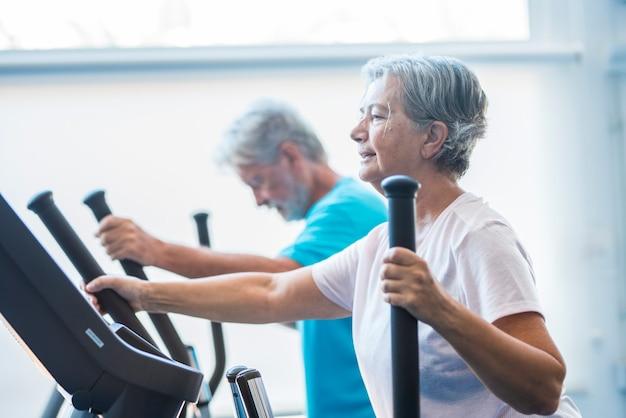 Frau mit einem precor im fitnessstudio - aktiver senior mit seinem mann im hintergrund - ein paar rentner, die zusammen übungen machen