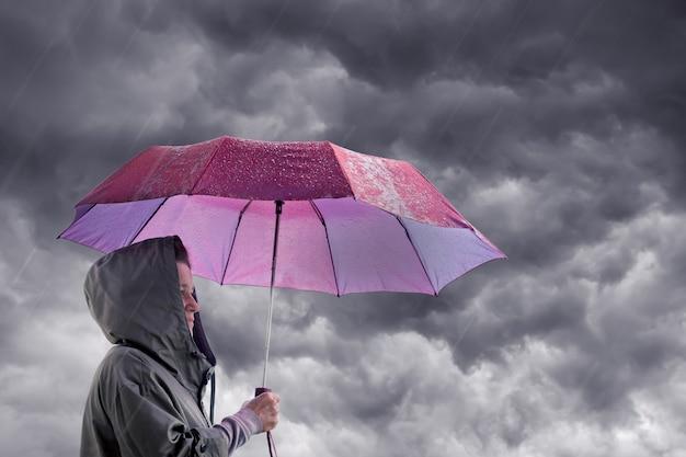 Frau mit einem regenschirm vor dem hintergrund eines dunklen stürmischen himmels