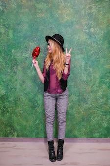 Frau mit einem roten ballonherz am 14. februar valentinstag.