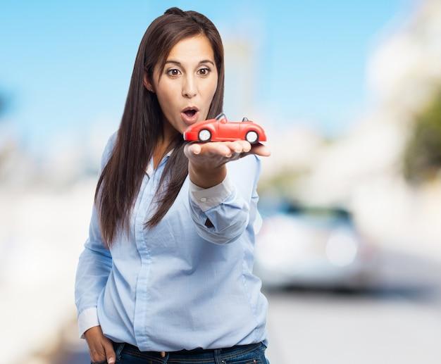 Frau mit einem roten spielzeugauto mit unscharfen hintergrund