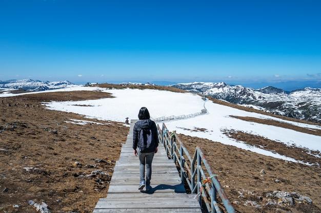 Frau mit einem rucksack geht auf die schneeberge