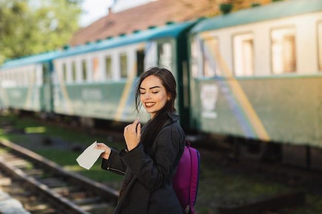 Frau mit einem rucksack, in der nähe des zuges prüft seine fahrkarte zum bahnsteig