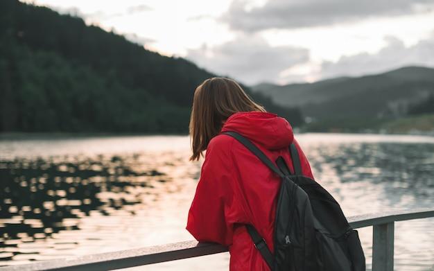 Frau mit einem rucksack in einem roten regenmantel, der den blick auf den see und den tannenwald genießt