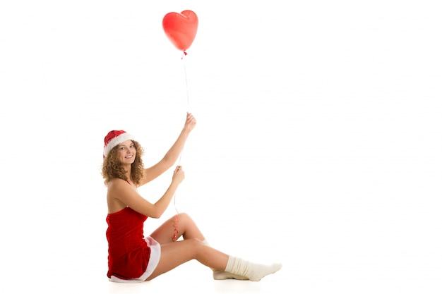 Frau mit einem sankt-kostüm und einem roten ballon