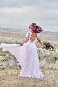 Frau mit einem schönen blumenstrauß in ihren händen tanzen auf dem berg in den strahlen des morgengrauen-sonnenuntergangs. schönes weißes langes kleid auf dem mädchenkörper