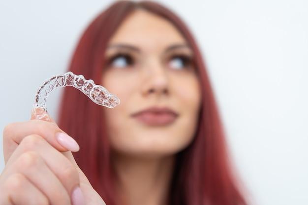 Frau mit einem schönen lächeln zeigt einen transparenten mundschutz