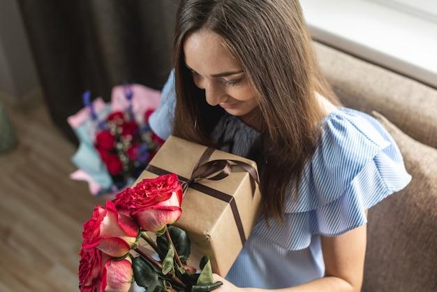 Frau mit einem schönen strauß frischer rosen und einer geschenkbox in ihren händen zu hause