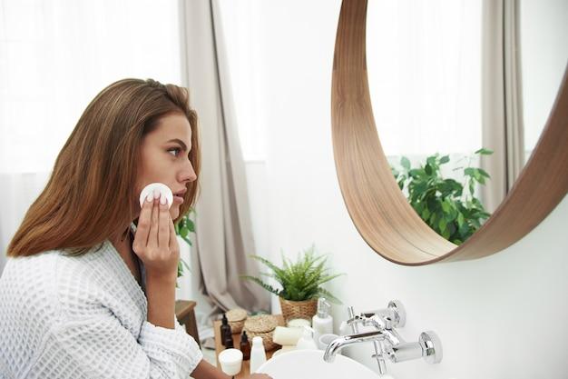 Frau mit einem schwammwattepad problemhaut. ein bild eines glücklichen mädchens, das ihr gesicht mit wattepads über badezimmer säubert. schönes gesicht der jungen frau mit sauberer frischer haut.
