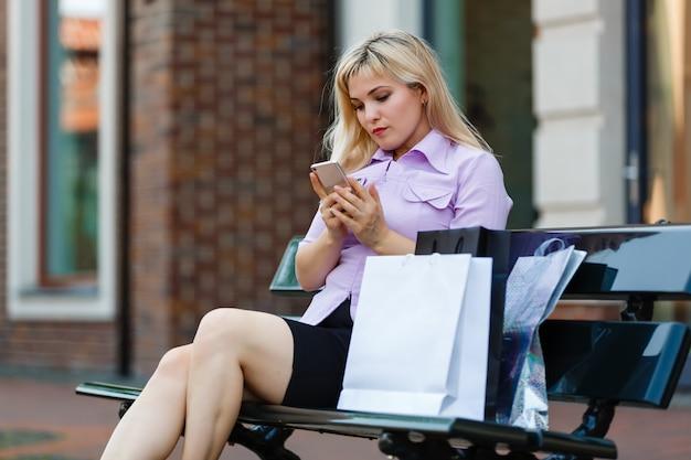 Frau mit einem smartphone, der auf einer bank an einem sonnigen tag sitzt