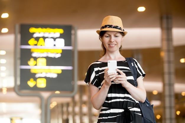 Frau mit einem smartphone in flughafen