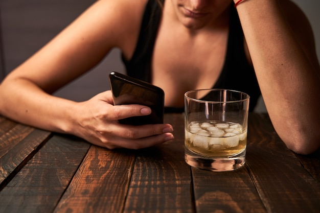 Frau mit einem smartphone und einem glas alkohol an einer bar. konzept des alkoholismus.