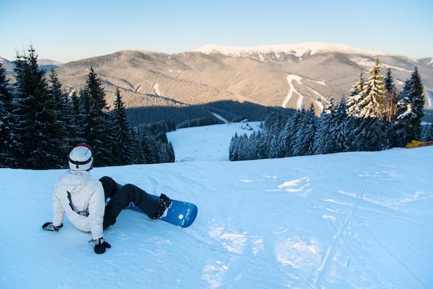 Frau mit einem snowboard, das auf der frischen schneespitze eines berges sitzt, der die landschaft eines skigebiets genießt.