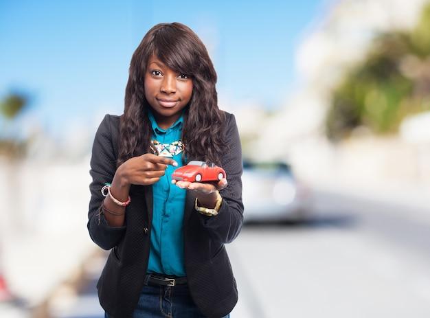 Frau mit einem spielzeugauto in der hand