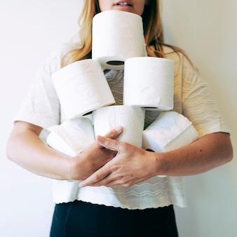 Frau mit einem stapel toilettenpapierrollen