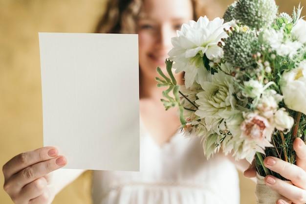 Frau mit einem strauß weißer blumen mit einer karte