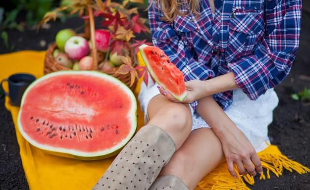 Frau mit einem stück reifer wassermelone in einem picknick