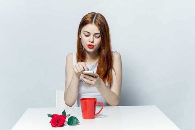 Frau mit einem telefon in ihren händen, die einen tisch mit einer rosenblume fotografieren