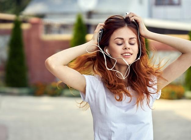 Frau mit einem telefon in kopfhörern läuft