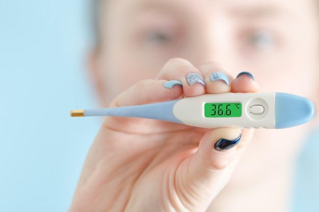 Frau mit einem thermometer in der hand. normale körpertemperatur: 36,6