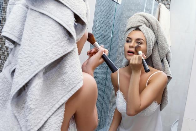 Frau mit einem tuch auf ihrem kopf, schauend im spiegel und das zutreffen bilden