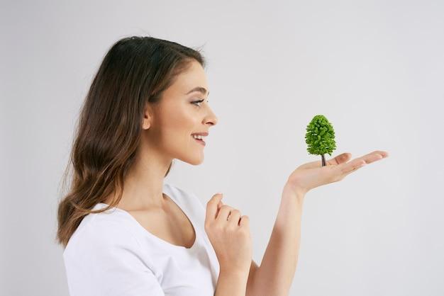 Frau mit einem wachsenden baum in der hand