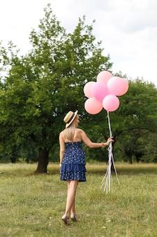 Frau mit einem weidenkorb, einem hut, rosa ballonen und blumen gehend auf eine landstraße