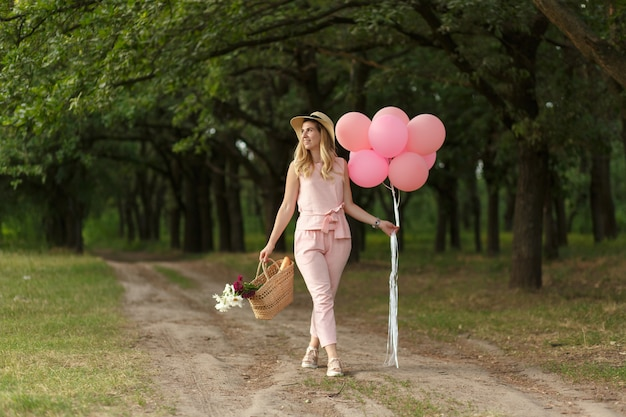 Frau mit einem weidenkorb, einem hut, rosa ballons und blumen, die auf eine landstraße gehen