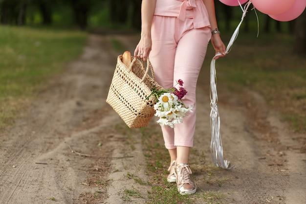 Frau mit einem weidenkorb, einem hut, rosa ballons und blumen, die auf eine landstraße gehen.