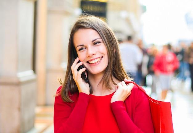Frau mit einem weihnachts-outfit einkaufen, während zu fuß und am telefon sprechen