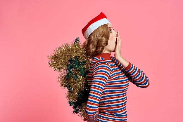Frau mit einem weihnachtsbaum in ihrem rücken